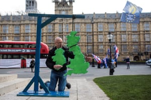 A pro-Brexit protester erects a model of the British Isles hanging from gallows in London, UK