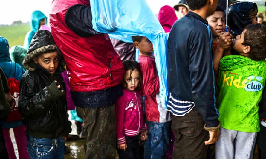 Migrants and refugees wait in line under the rain for food distribution at the makeshift camp in the northern border village of Idomeni, Greece.