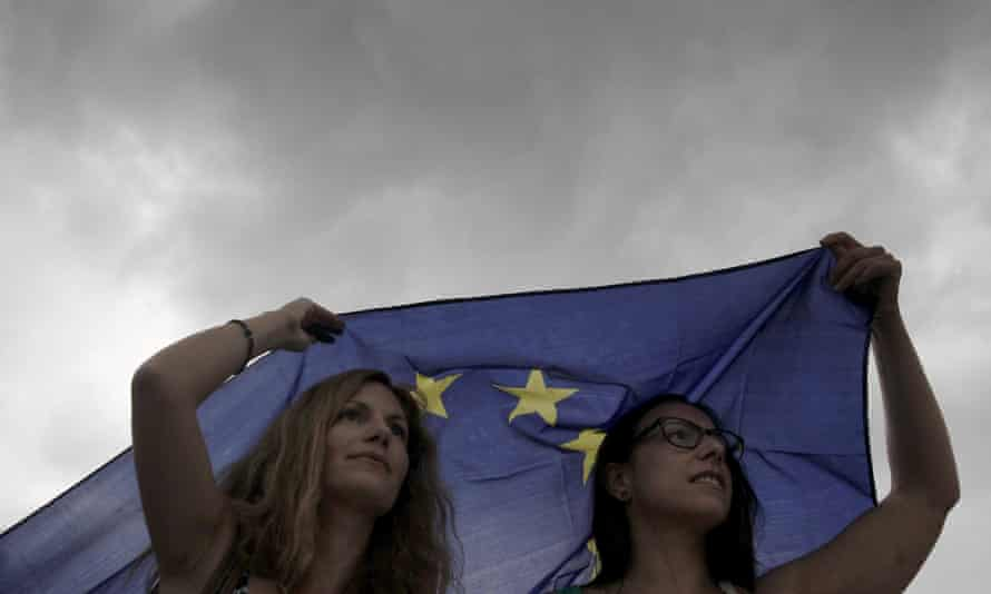 Greek protesters sheltering from rain under an European Union flag