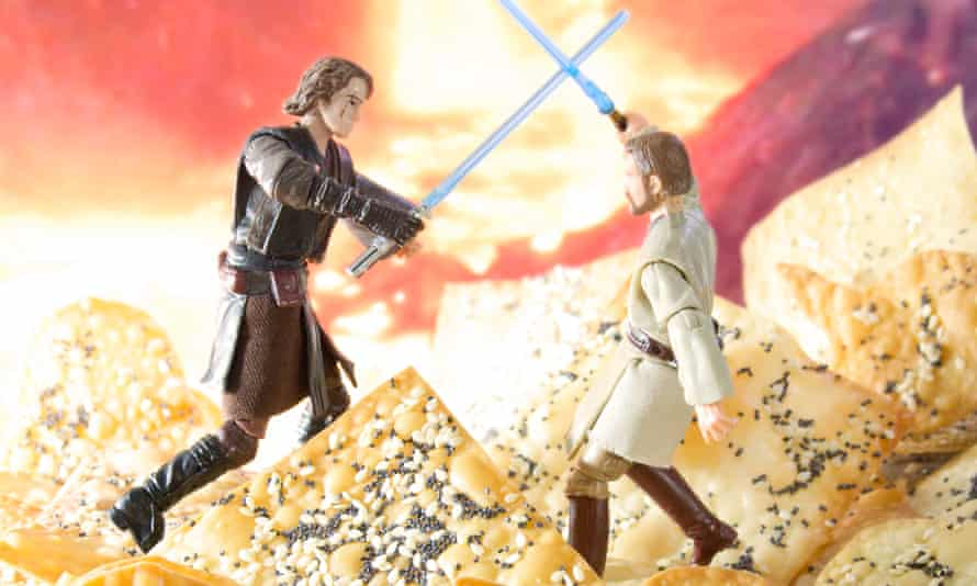 Two tiny Stars Wars figurines fighting with lightsabers standing on top of giant Obi Won Ton biscuits