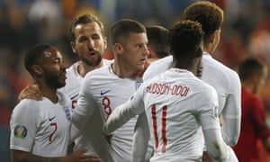 England players hug teammate Ross Barkley, center, after he scored his side's third goal.