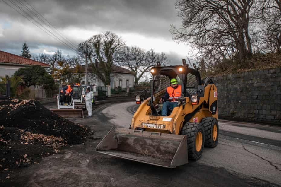 Workers near the village of Zafferana Etnea clean volcanic sand from the main streets