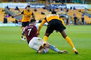 Wolves' Nelson Semedo clips John McGinn in the box.
