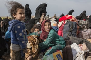 Civilians fleeing from Islamic State's last remaining territory in Syria after two days of heavy fighting wait to be taken to an internment camp