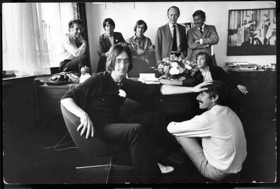 Apple in June 1968. Back row (L-R) includes Denis O'Dell, Paul McCartney, Alexis Mardes, Peter Brown (behind John Lennon's head), Brian Levis and Ron Kass; Neil Aspinal sits in the middle ground; in the foreground, John Lennon and Derek Taylor.