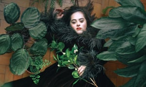 A woman with Down's syndrome in a black velvet dress with a furry collar, lying on her back with green leaves around and on her