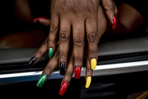 Flint resident Tracy Palmer shows off her Juneteenth-inspired nails during one of two parades celebrating the holiday along Saginaw Street in downtown Flint, Michigan