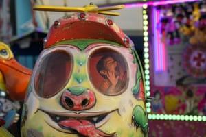 Titu, Romania: a child laughs while on a ride at an autumn fair