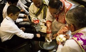 A priest washes a boy's feet during Maundy Thursday mass at Mar Hanna church