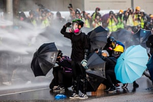 Protesters try to shield themselves from the water cannon