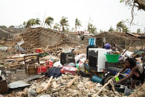 A woman hangs a cloth to dry in a sea of rubble in the Praia Nova area of Beira