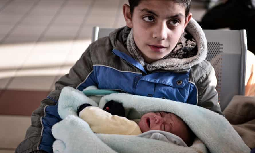 A boy holds his baby brother at the port of Piraeus on Tuesday