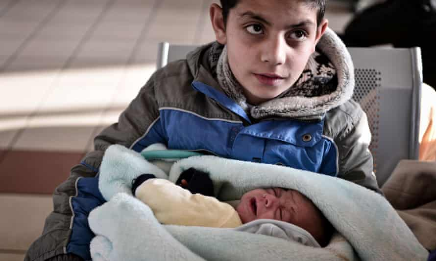 A refugee boy holds his baby brother at the port of Piraeus, Greece, in February 2016.
