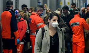 A passenger wears a surgical mask after a temperature check by health worker as she arrived from Milan Bergamo at Krakow international airport on Wednesday.