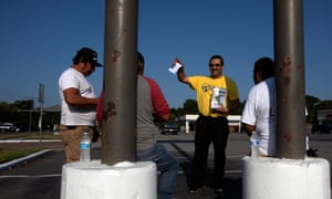 Alejandro Zuniga of the Fe y Justicia Worker Center offers water and literature to day laborers in Houston, where the Hurricane Harvey recovery has been marred by abuses of workers' rights.
