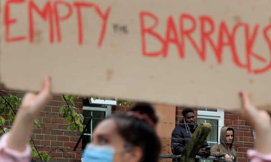 Asylum seekers watch a solidarity event outside Napier barracks