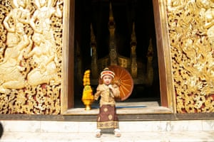 A girl wears traditional dress poses for a photo in a temple during the New Year festival in Luang Prabang