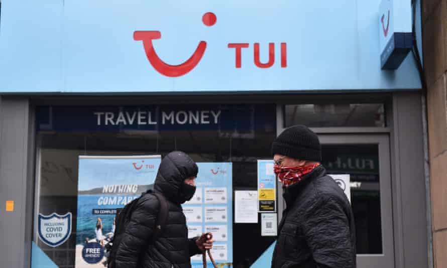 Two men walk past a Tui travel centre in Congleton