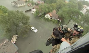 Two rescuers from US navy helicopter sea combat squadron 7 are lowered to a house in Beaumont.