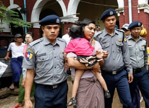 Kyaw Soe Oo, escorted by police, holds his daughter as he leaves court during a break