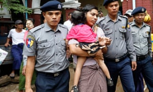 Kyaw Soe Oo, escorted by police, holds his daughter as he leaves the court during a break on 18 June