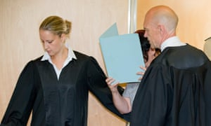 Andrea G​öppner hides her face as she arrives with her lawyers at the district court of Coburg, Germany.