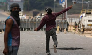A man throws stones at Venezuelan national guards troops, at the Brazilian border on Sunday.
