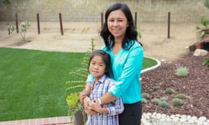 Yumi Wong and daughter Kayley in front of their new lawn, half grass and half drought-tolerant landscaping.