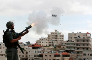 Jerusalem, 2010 an Israeli border police officer fires tear gas towards Palestinian stone-throwers
