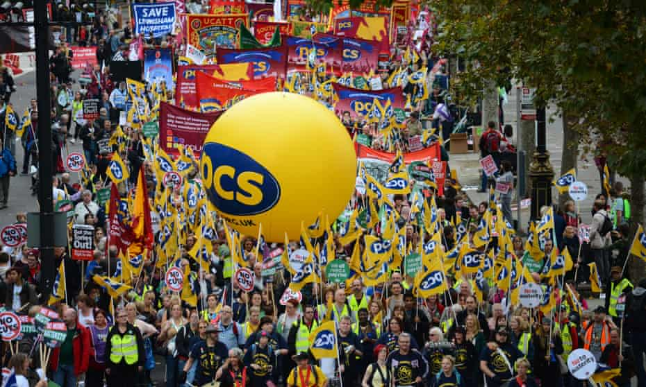 Trade unionists and supporters wave PCS union flags