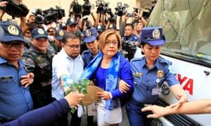 Philippine police escort Leila de Lima on her way to a local court in Quezon city, metro Manila.