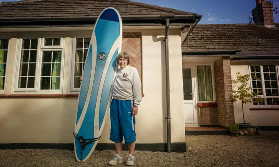 Gwyn Haslock, 71, holding her surf board vertically as she stands in front of her house in Cornwall