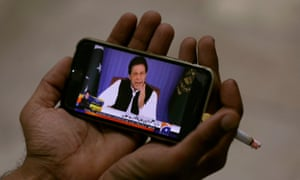 A man holds a phone showing Imran Khan speaking to the nation in his first televised address