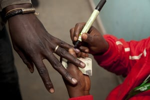 A polling official marks a voter's finger after casting his vote at a polling station in Nairobi