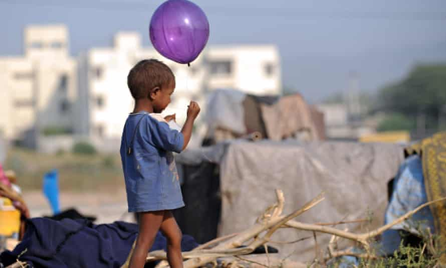 A Pakistani child plays with a balloon in front of his makeshift tent on the outskirts of Islamabad