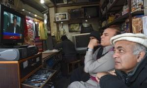 Pakistani shopkeepers watch Imran Khan's televised speech.