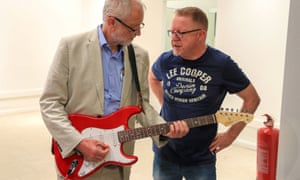 Labour leader Jeremy Corbyn tries out a guitar with John Newhouse of a local charity Trust Music during a visit to Bolton.
