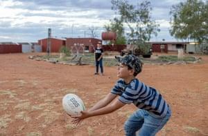 Jakobe Passmore, in striped shirt, and Izyric Passmore play footy near the Pilungah homestead