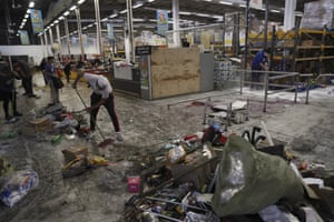Workers clean up a looted supermarket in Santiago