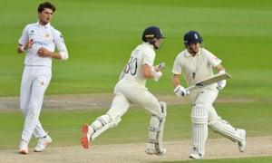 England's Ollie Pope and Joe Root run as Pakistan's Shaheen Shah Afridi looks on.
