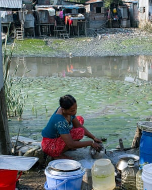A woman washes the dishes by the banks of the Kirtankhola River, Barishal.