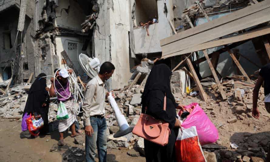 Yemenis carry belongings they recovered from the rubble of buildings destroyed during Saudi-led air strikes in Hodeida