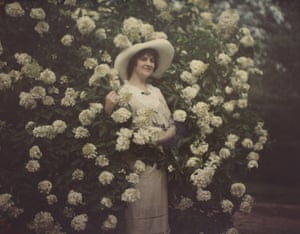 Woman standing in flowering bush, circa 1915