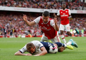 Harry Kane goes to ground under a challenge from Arsenal's Sokratis Papastathopoulos.