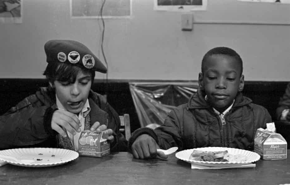 Two young boys eat during a free breakfast for children program sponsored by the Black Panther Party in 1969.