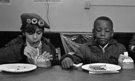 Two young boys eat during a free breakfast for children program sponsored by the Black Panther party, New York, winter 1969.