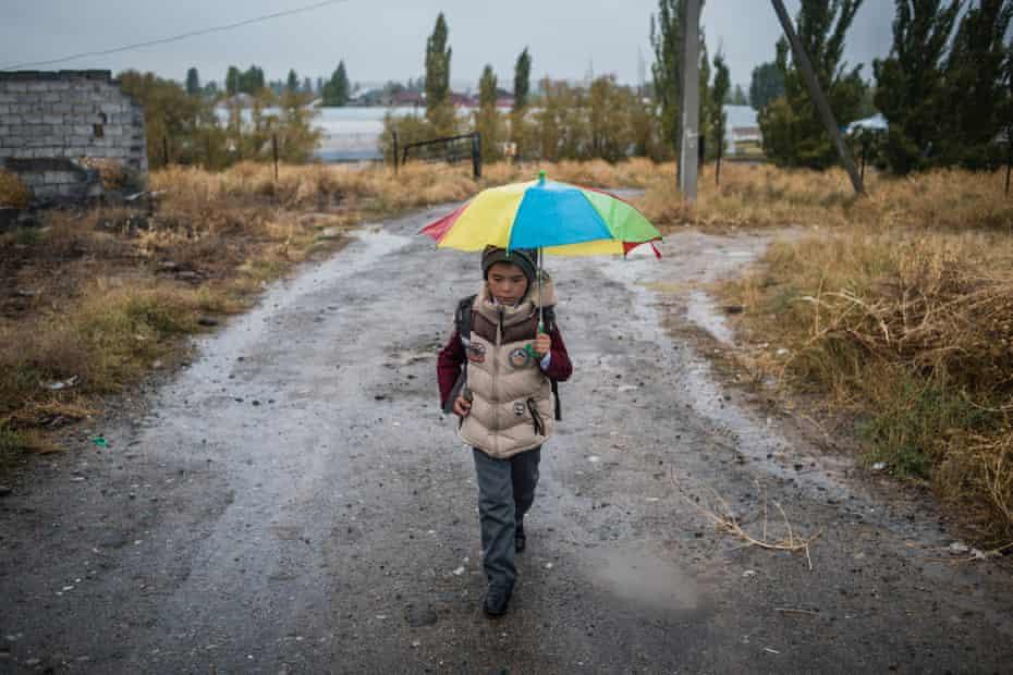 A boy from the Ak-Zhar novostroika walks across scrubland to school in Ak-Bata