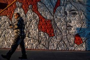 "A pedestrian walks past ""Contigo"" (With You) a mural by Christin Apodaca"