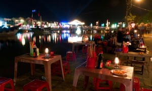Street food stalls by the Thu Bon river lit with lanterns at night, Hoi An, Vietnam.