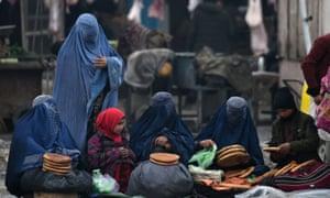 Afghan women sell bread on a street in Mazar-i-Sharif.
